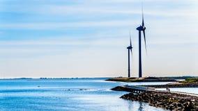 Turbinas eólicas na entrada de Oosterschelde na ilha de Neeltje Jans na barreira do impulso de tempestade dos trabalhos do delta foto de stock