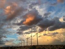 Turbinas eólicas no por do sol em uma exploração agrícola de energias eólicas Fotografia de Stock Royalty Free