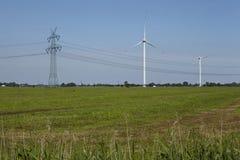 Turbinas eólicas, polo de poder e linhas elétricas Imagens de Stock Royalty Free
