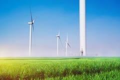 Turbinas eólicas sob o céu azul As turbinas eólicas que geram elegem Imagens de Stock