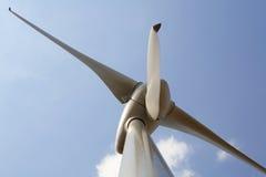 The Turbine. Detail of wind turbine against a blue sky. Slight motion blur on bottom rotor blade Stock Image