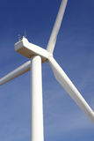 The Turbine. Wind turbine with control cublicle against blue sky. Slight motion blur on blades Royalty Free Stock Image