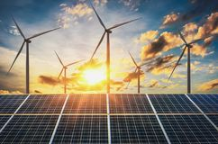 turbine de vent avec les panneaux solaires et le coucher du soleil concept propre photos libres de droits