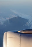 Turbine Engine with volcanic mountain surrounded by clouds in the background. Turbine Engine with pointy volcanic mountain surrounded by clouds visible in the Stock Images
