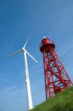 Turbine and Lighthouse. User and Producer. A red steellighthouse and a white steel turbine standing next to eachother, taken from a low point of view Royalty Free Stock Image