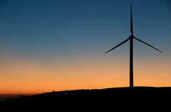 Turbine in Twighlight. A wind turbine and grazing sheep silhouetted against the gloaming sky on a hill farm in Rhondda, Wales Royalty Free Stock Photography