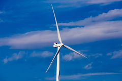 Turbine windmills for generating electricity in environmentally friendly way are installed in field.  stock images