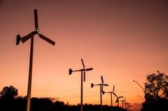 Turbinen mit Stromleitung im Sonnenuntergang stockbild