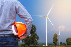 Turbiner för vind för framdel för hjälm för säkerhet för guling för teknikerställningsinnehav som frambringar elektricitet Arkivfoto