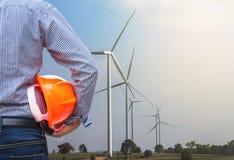 Turbiner för vind för framdel för hjälm för säkerhet för guling för teknikerställningsinnehav som frambringar elektricitet Arkivbild