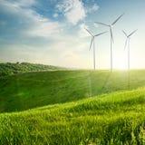 Turbiner för vindgeneratorer på solnedgångsommarlandskap arkivbilder