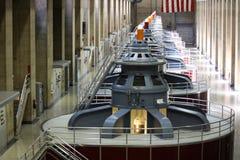 Turbines énormes dans une rangée à l'intérieur de du barrage de Hoover au loin A Photo stock