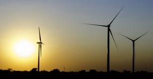 Turbines d'énergie éolienne dans le coucher du soleil Photos stock