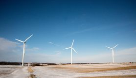 Turbines de moulin à vent dans une rangée contre le ciel bleu un jour d'hiver Photo stock