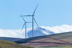Turbines de vent avec des montagnes et des nuages à l'arrière-plan Image libre de droits
