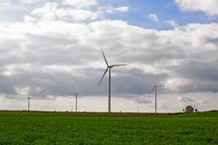 Turbines de vent avec le champ vert et le ciel nuageux photo stock