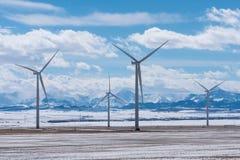 Turbines de vent avec Rocky Mountains pendant l'hiver Photographie stock libre de droits