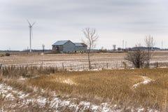 Turbines de vent dans classées en partie couvert en neige et ciel nuageux Image libre de droits