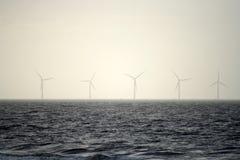 Turbines de vent dans le brouillard de mer Photographie stock libre de droits