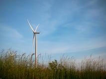 Turbines de vent dans le domaine d'herbe avec le ciel bleu photographie stock