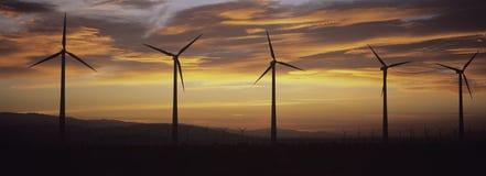 Turbines de vent de silhouette au coucher du soleil Image libre de droits
