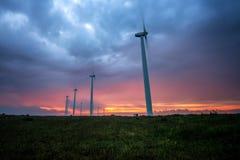 Turbines de vent produisant de l'électricité contre le lever de soleil image libre de droits