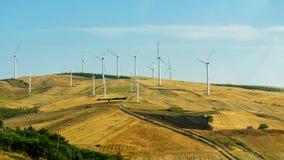 Turbines de vent produisant de l'électricité sur le champ sous le ciel bleu photos libres de droits