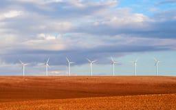 Turbines de vent sous un ciel orageux Photo stock