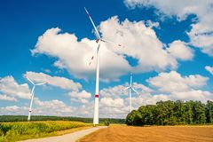 Turbines on field on cloudy blue sky. Wind farm in Lower Saxony, Germany. Global warming, climate change. Alternative energy source. Eco power, green royalty free stock photography