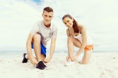 turbines Jeunes couples s'exerçant et stertching sur la plage Photographie stock libre de droits