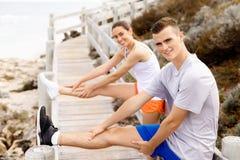 turbines Jeunes couples s'exerçant et stertching sur la plage Image libre de droits