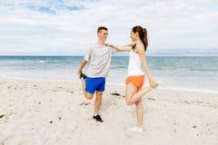 turbines Jeunes couples s'exerçant et stertching sur la plage Photos libres de droits