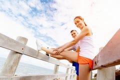 turbines Jeunes couples s'exerçant et stertching sur la plage Photos stock