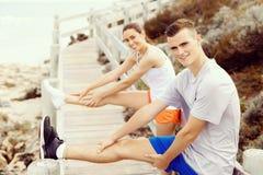 turbines Jeunes couples s'exerçant et stertching sur la plage Images libres de droits