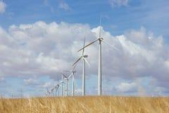 Turbines in a windfarm. Generating alternative energy on wheat field Stock Image