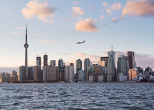 Turbo prop aircraft landing at Billy Bishop airport. Toronto skyline at sunset with a small turbo prop aircraft plane which is flying over city. It is coming in royalty free stock images