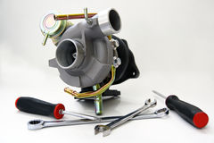 Turbo and tools. A turbocharger has been assembled and ready to be installed onto a vehicle Royalty Free Stock Photo