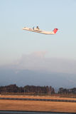 Turboprop airplane takes off while volcano erupts Royalty Free Stock Images