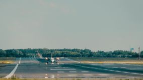 Turboprop commercial airplane landing at the airport beyond heat haze. Propeller commercial airplane landing at the airport stock footage
