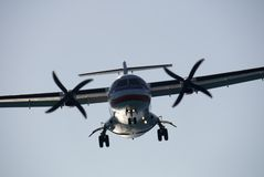 Turboprop Landing 1. A twin-engined turboprop passenger plane landing at dusk stock photography