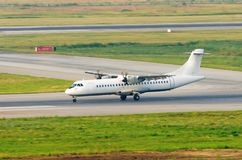 A turboprop passenger plane lands on the runway at the airport, the reverse. A turboprop passenger plane lands on the runway at the airport, the reverse Royalty Free Stock Photo