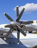 Turboprop transport aircraft against. The blue sky closeup Stock Image