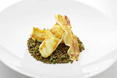 Turbot fillet with lentils and crispy bacon Royalty Free Stock Photography