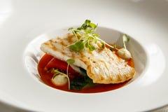 Turbot grillé, tabouli, sauce au poivre douce et légumes d'été Plat blanc Image stock