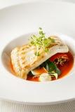 Turbot grillé, tabouli, sauce au poivre douce et légumes d'été Plat blanc Images stock