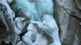 Turbulent Creek and Rocks. Clear, fresh mountain water tumbles over boulders worn smooth by the turbulence stock video footage