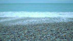 Turbulent foamy sea waves splashing ashore on pebble beach in slowmotion. Stock footage stock video