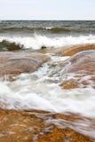 Turbulent sea. A photo of sea waves foaming on the large orange rocks Royalty Free Stock Photos