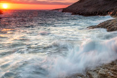 Turbulent sea under a fiery orange sunset. Or sunrise with waves breaking on a rocky shoreline sending up clouds of white spray with the glowing orb of the sun stock photos