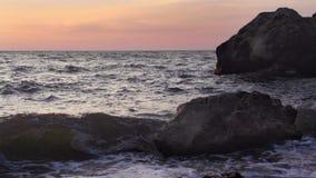 Turbulent vatten på en stenig kustlinje arkivfilmer